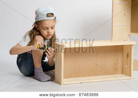 Little Girl In Overalls Collector Of Furniture Making Box On The Dresser