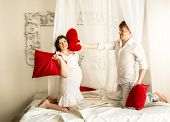 Happy pregnant woman having pillow fight with husband on bed with baldachin poster