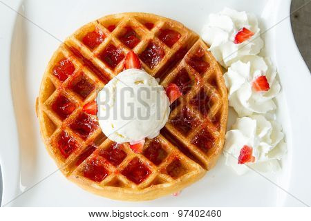 Strawberry waffle icecream toping on white plate.