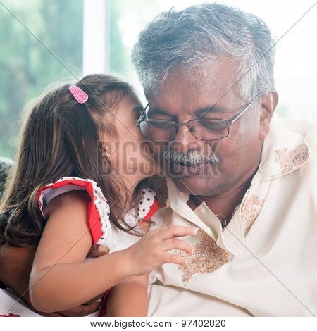 Portrait of Indian family at home. Grandchild kissing grandparent. Grandfather and granddaughter. Asian people living lifestyle.
