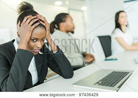Young Stressed Businesswoman Battling With A Headache During A Business Conference