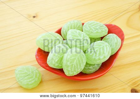 Woodruff candies in a red porcelain dish on wooden table poster
