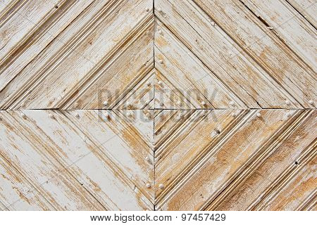Rhomb pattern of the old weathered white-painted wooden gate.