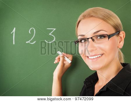 Closeup portrait of young beautiful teacher wearing glasses writing numbers on green chalkboard, start of education season, back to school