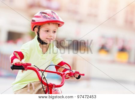 Little boy playing outdoors, cute cheerful child having fun in summer camp, nice kid riding on red stylish bicycle on blur urban background, enjoying carefree summer holidays