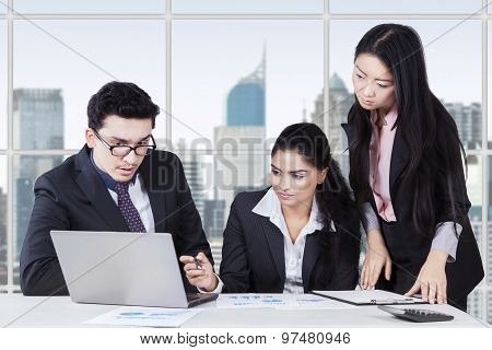 Three Entrepreneurs Working On Desk In Office