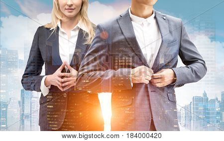 Unrecognizable blond businesswoman and a businessman buttoning his suit are standing against a morning city panorama. Toned image double exposure