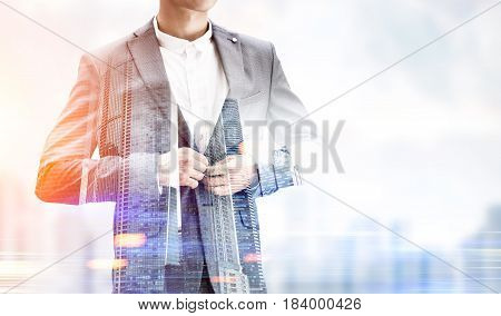 Close up of an unrecognizable businessman buttoning his suit standing against a blurred city panorama. Mock up toned image double exposure
