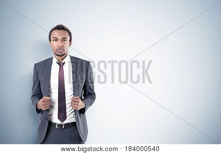 Portrait of a serious African American businessman with a beard wearing a gray suit and a tie standing near a gray wall. Mock up