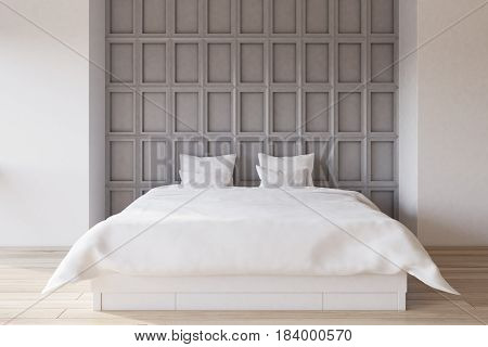 Interior of a bedroom with white and gray wooden wall element and a double bed with white bedding. 3d rendering.
