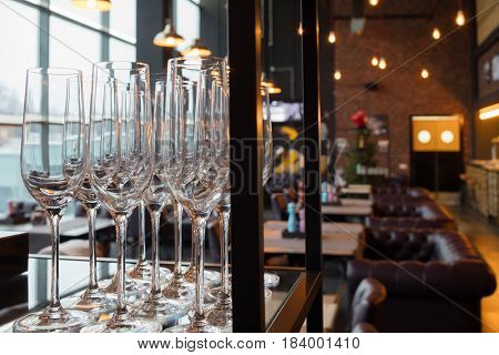 Shiny glasses are on shelf in stylish empty restaurant, shallow dof