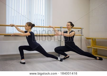 Pretty woman and girl in black do exercises at ballet bar in hall