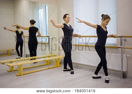 Woman and girl do exercises at ballet bar in hall with mirror