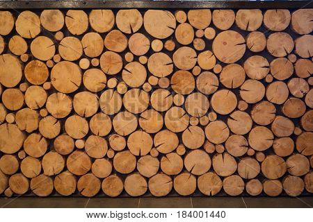 Logs of trees, pile of yellow round wood logs, this is decoration of bar counter