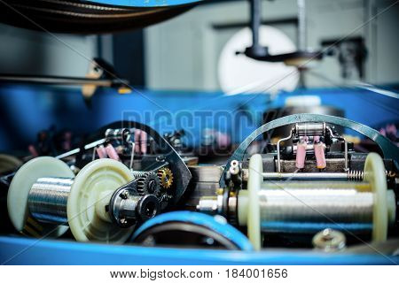 The mechanism of a braiding machine close-up. Modern equipment for making braids from metal alumino-copper wire.