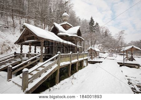Wooden old-style structure with baptistery in Russian Orthodox Monastery at winter day