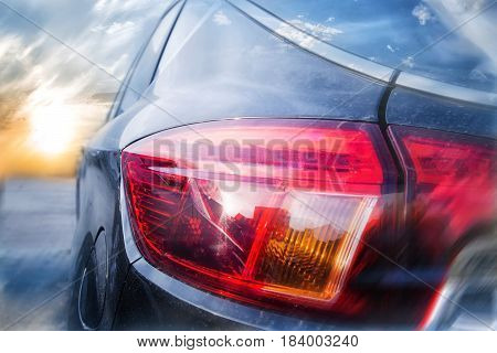 A collage of a back lantern of the car and a rising sun in a background with a shallow depth of field