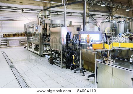 Filling and labeling beer bottles. Brewing production. Abstract industrial background. Brewery shop.