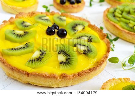 Tartlets tartas from custard kiwi and black currant on a white wooden background.