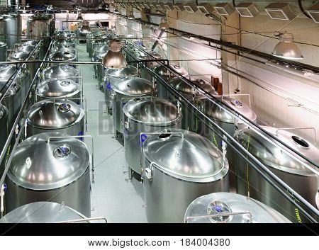 Industrial shop with a lot of metal tanks, built in long rows. Modern food production.
