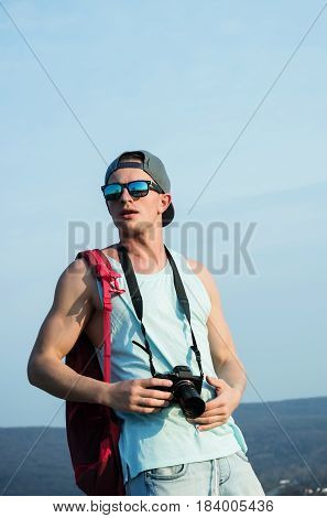 Caucasian man young traveler or photographer with camera in muscular hands triceps biceps in stylish sunglasses and cap red backpack standing on sunny day on blue sky. Leisure and summer vacation
