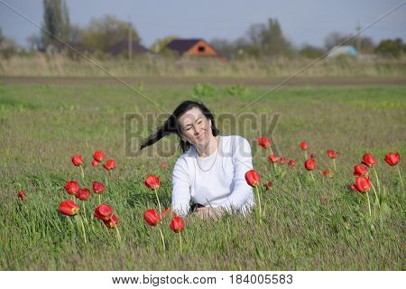 Beautiful Fairy Young Girl In A Field Among The Flowers Of Tulips. Portrait Of A Girl On A Backgroun