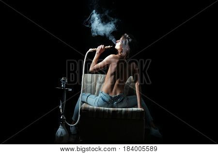 pretty sexy woman smoking hookah girl with naked back and body in jeans sitting on eastern chair with shisha bong or kalian as arabic tradition on black background
