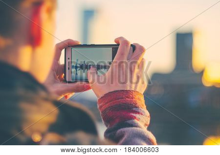 Young woman takes pictures of the sunset in the city on a smartphone. City travel concept