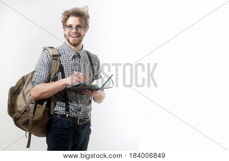 backpack and notebook pen at happy man or student traveler with beard and stylish hair in nerd glasses smiling in checkered shirt jeans on white background. Education and travelling copy space