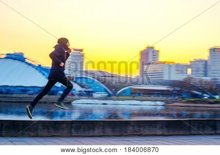 Silhouettes a young man on a run in the city on the embankment during sunset. Blur in motion abstract image of a man's silhouette