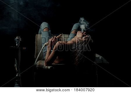 arabic tradition naked girl smoking hookah pretty woman with sexy back and body in jeans sitting on eastern chair with shisha bong or kalian on black background