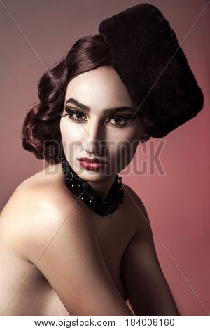 Portrait of beautiful naked fashion model with wavy hair style, hat and dark makeup on red background.