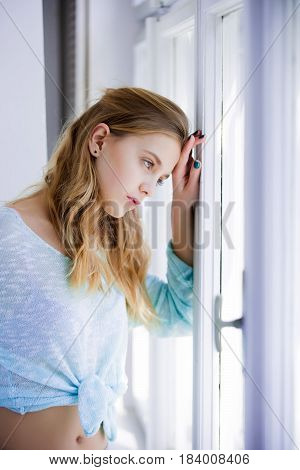 Beauty and fashion Pretty girl or young woman with cute face and blond long hair in stylish blue clothes looking out of window on sunny day. Future perspective and outlook