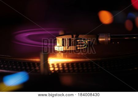 Moving pickup or audio cartridge playing on retro vinyl disc on record player or turntable phonograph device with colorful bokeh lights on black background. Music and entertainment