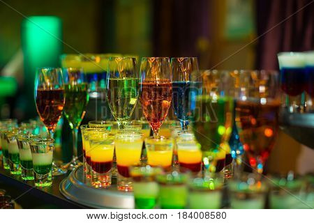 cocktail colorful background in night club on table top in bar mix alcoholic drink in glass at restaurant party