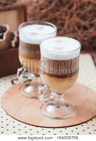 Latte macchiato with coffee beans with coffee background copy space