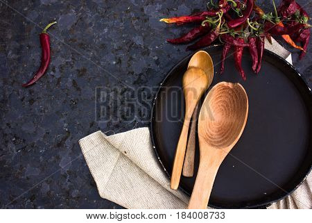 A kitchen utensils and pan with spice. Background black marble. view from above. Space for text
