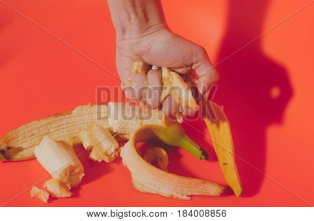 Female hand squeezing juice or squash from banana ripe mellow fruit and peeled yellow skin on bright orange background. Vitamin and healthy eating