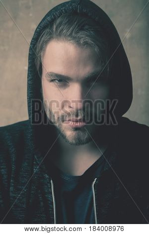Bearded man or handsome model with stylish beard and serious face wearing fashionable grey hoodie sweatshirt with hood on head on beige concrete wall. Geek culture and fashion