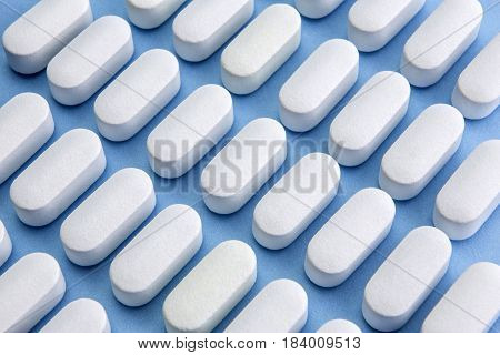 Some pills aligned in the form of flecla isolated on blue background