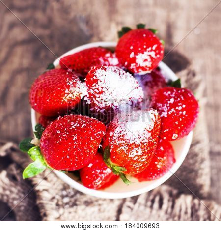 Ripe red strawberries with sugary on wooden table. Fresh strawberries in a bowl with copy space