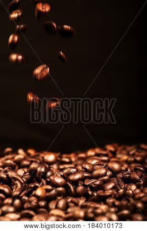 Falling coffee beans close up over black background
