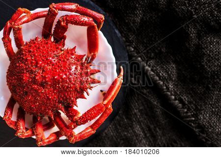 Delicious seafood - Red crab on white plate and rustic sack cloth background.