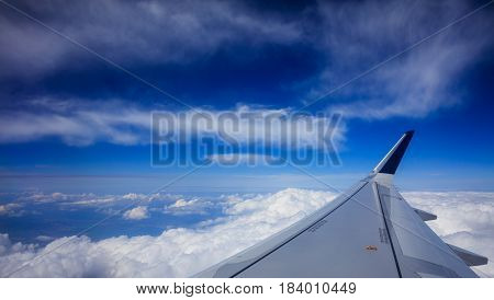 Plane Wing Over Clouds On A Blue Sky Background