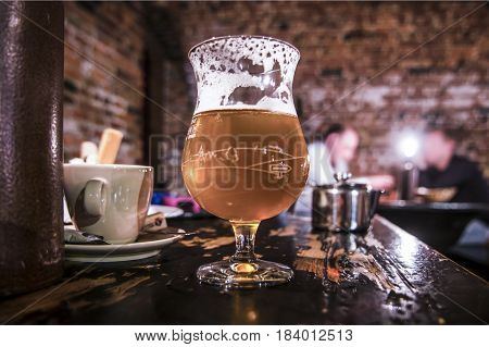A glass of light beer on a table in an old pub,