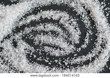 white crystals sea salt isolated on black background. sprinkled salt shakers of white salt. shot selective focus. Sifting coarse scattered sea salt on stone close up.