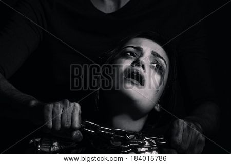 Young woman subjected to violence in darkness