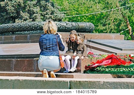 Volgograd Russia - May 09 2016: Mother taking pictures of daughters dressed as Russian Soviet soldier of World War II at eternal fire on Victory day in Volgograd