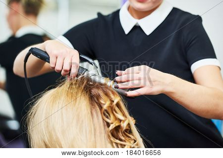 hairdo in beauty salon. hairdresser making coiffure with curl to wonam