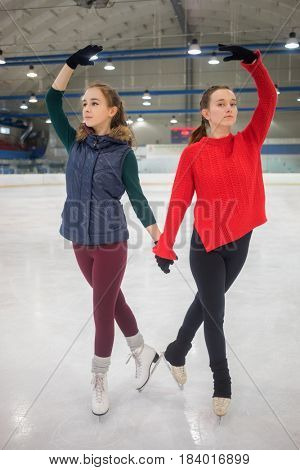Two pretty slim graceful girls pose on skate in indoor ice rink